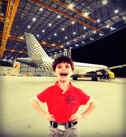 Child wearing an original aircraft seat belts in a plane hangar